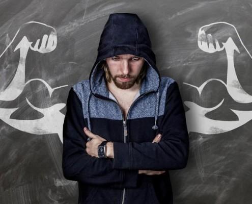 Mann steht vor Tafel mit aufgezeichneten starken Armen