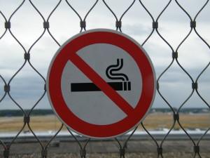 Schild an Zaun mit durchgestrichener Zigarette