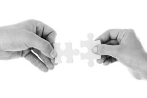 Zwei Hände halten zueinander passende Puzzleteile