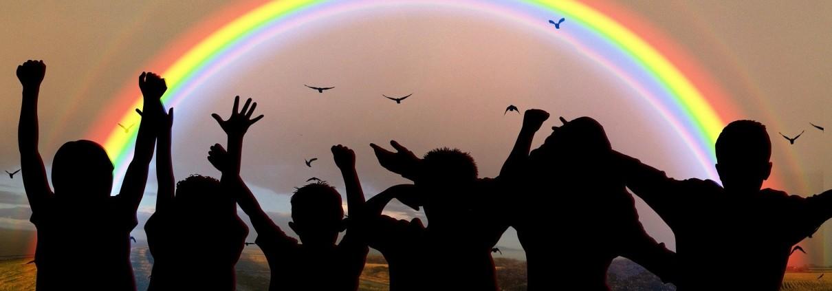 Jubelnde Menschen unter Regenbogen