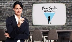 """Frau zeigt auf Schrift """"Be a leader, not a boss"""""""